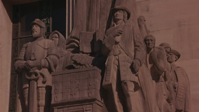 medium angle of statue in front of capitol building in baton rouge, louisiana. woman in robes, helmeted man with sword. government buildings. religious. - kapitol von louisiana stock-videos und b-roll-filmmaterial