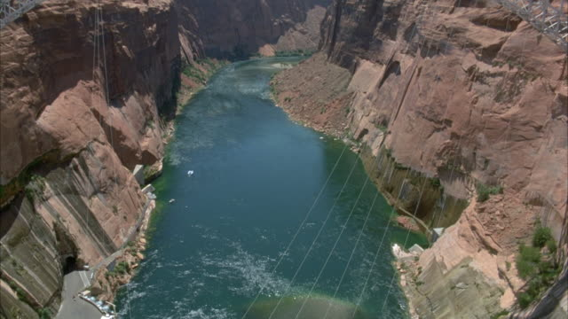 est shot. high angle down of glen canyon dam. see water surrounded by steep canyon walls. - glen canyon staudamm stock-videos und b-roll-filmmaterial