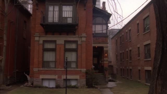 medium angle establishing shot of three story brick house. see brick buildings very close on both sides of house. - brick house stock videos & royalty-free footage