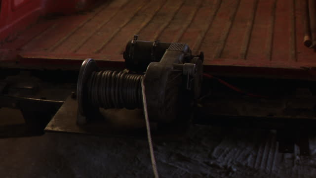 MEDIUM ANGLE OF WINCH AFFIXED TO TRUCK'S FLATBED, REELING IN A CABLE, GETTING STUCK.