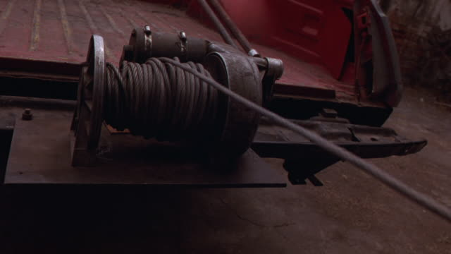 CLOSE ANGLE OF WINCH AFFIXED TO TRUCK'S FLATBED, CABLE UNWINDING QUICKLY.