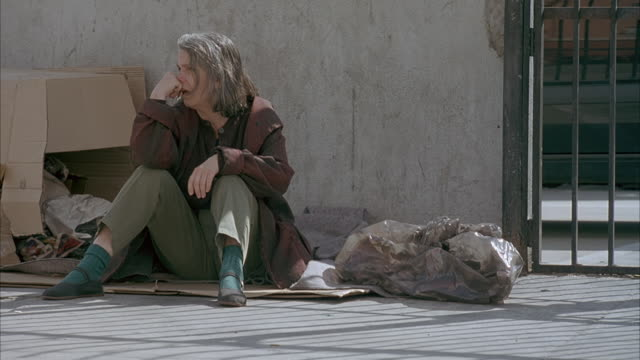 medium angle of homeless woman sitting on cardboard pieces on sidewalk. woman has hand on chin, cars pass by in foreground. - 1990 1999 stock videos & royalty-free footage