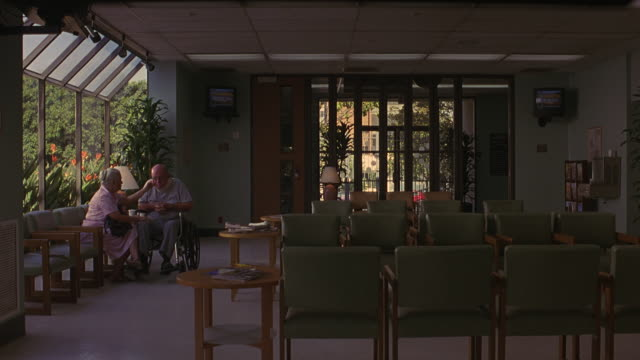 stockvideo's en b-roll-footage met wide angle waiting room of retirement home, medical center, or hospital. rows of chairs, man in wheelchair, television sets on walls. - woongemeenschap ouderen