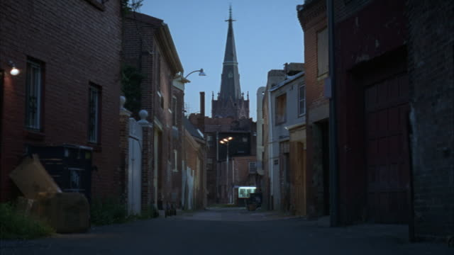 wide angle  of alley lined with two-story brick houses or buildings. old church steeple visible in background. - zweistöckiges bauwerk stock-videos und b-roll-filmmaterial