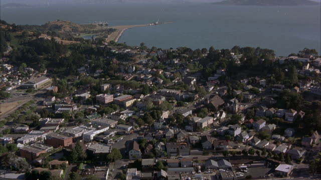 vídeos y material grabado en eventos de stock de aerial over point richmond on northern san francisco bay. looks like small town. low rise buildings. zoom on brick building, the mac hotel, then pulls back. - richmond