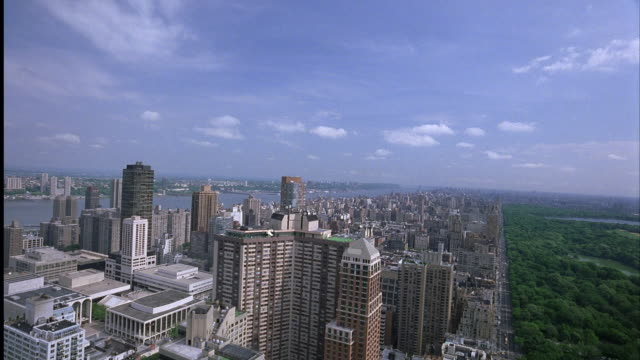 aerial, wide angle. camera mounted on track on top of high rise building. looking out over downtown manhattan and central park. camera is pulled right along track, falls down side of building. stops midway down, see buildings and hotel. - anno 2001 video stock e b–roll
