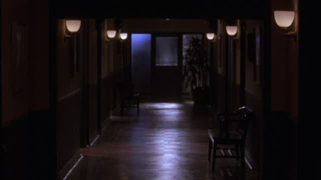 stockvideo's en b-roll-footage met wide angle of a dimly lit hallway at night.  a few chairs lines the dark wood colored hall.  could be an apartment building, an old fashioned office, or a 1950s style detective agency or office. - detective