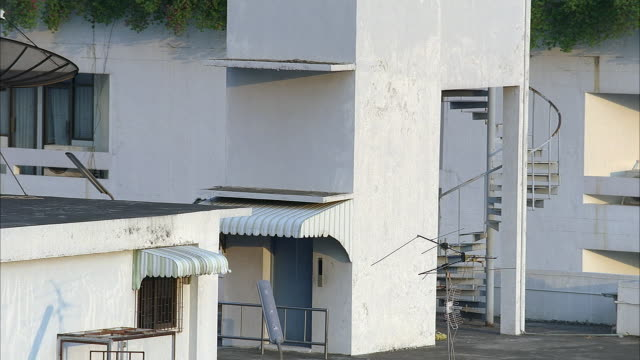 medium angle of side of white apartment building. see spiral staircase and exit doors. - spiral staircase stock videos & royalty-free footage