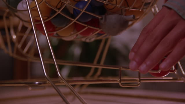 CLOSE ANGLE OF TRAP OF GOLD METAL BINGO CAGE WITH MULTI-COLORED MARKED BINGO BALLS INSIDE.  SEE HAND GRAB RED BALL FROM TRAP.