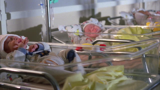 stockvideo's en b-roll-footage met medium angle of newborn babies in glass bassinets, babies are squirming, pans left to nearest baby, camera flashes go off. - wieg