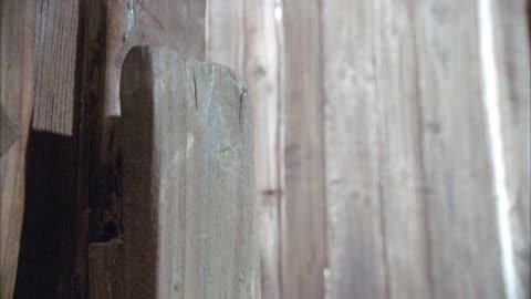 close angle of a wooden door and door handle. door looks old. might be barn or shack door. - barn stock videos & royalty-free footage
