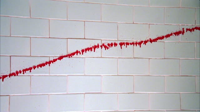 vídeos de stock, filmes e b-roll de pan left to right of blood splattered on block wall in basement. crime scene. - sangue