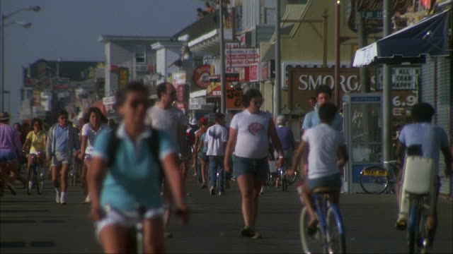 MEDIUM ANGLE OF CROWD AND BICYCLES ON BEACH BOARDWALK APPROACHING FRONT.