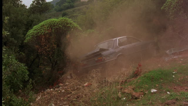 TRACKING SHOT OF 1985 BMW 520I SEDAN DRIVING OVER EDGE OF CLIFF OR HILLSIDE. CAR TUMBLES, SPINS, AND CRASHES DOWN HILL.