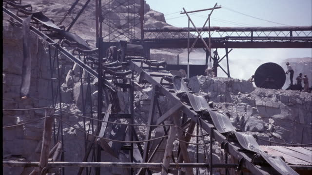 medium angle of mine. see miners or workers using old wooden mine equipment. two miners work on turning an oversized wheel. small bridge runs across rocky mine. blue sky in the background. - 1914年点の映像素材/bロール