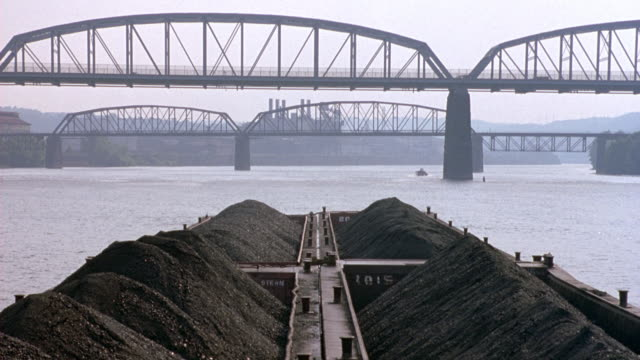 WIDE ANGLE OF BRIDGES OVER RIVER. SEVERAL CARS CROSS OVER BRIDGES. BOAT, BARGE FILLED WITH COAL IN FOREGROUND. INDUSTRIAL AREA IN BACKGROUND. SMOGGY. COAL BARGE.