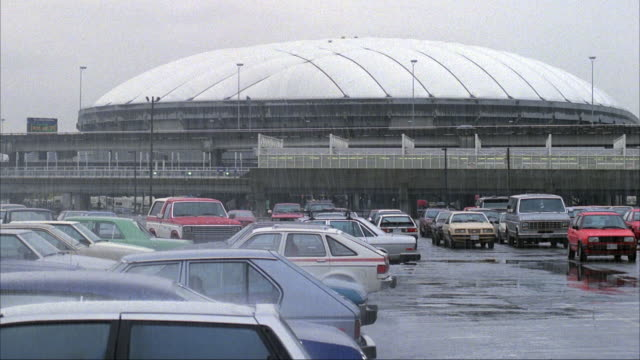 MEDIUM ANGLE OF BC PLACE STADIUM OR DOMED BUILDING WITH PARKING LOT IN FOREGROUND. HEAVY RAIN.