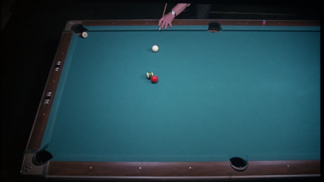 MEDIUM HIGH ANGLE DOWN OF POOL TABLE. MAN PERFORMS POOL TRICK AND MAKES THREE BALLS IN CORNER POCKETS AND SIDE POCKET.