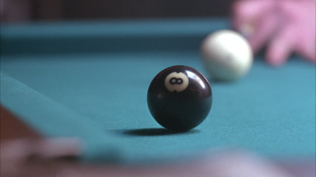 vídeos de stock e filmes b-roll de close angle of pool table, white ball hits 8-ball into corner pocket. - mesa de bilhar