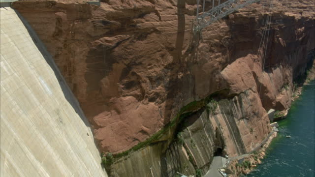 high angle down of glen canyon dam. see red rocky cliff next to dam. - glen canyon staudamm stock-videos und b-roll-filmmaterial