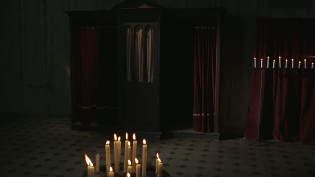 wide angle of confessional booth with red curtains in cathedral or church. surrounded by candles with glowing flames on candelabras. tile floor. - kirche stock-videos und b-roll-filmmaterial
