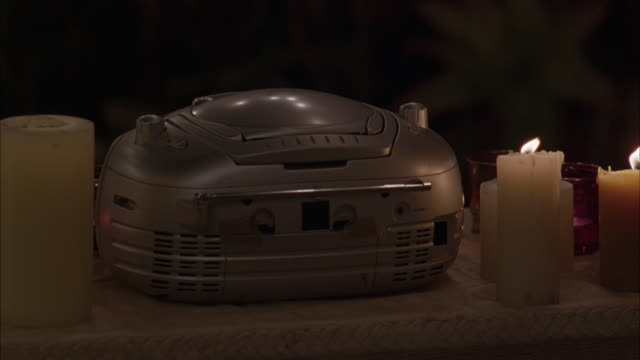 CLOSE ANGLE OF CD PLAYER BOOMBOX ON A TABLE. TABLE COVERED WITH WHITE CLOTH. LARGE LIGHTED CANDLES SIT NEXT TO CD PLAYER. CANDLE FLAMES DANCE AND CURTAIN BLOWS INTO FRAME. COULD BE ROMANTIC DINNER OR DATE.