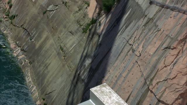 high angle down of glen canyon dam. rocky cliffs next to water. - glen canyon staudamm stock-videos und b-roll-filmmaterial