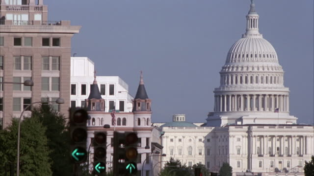 MEDIUM ANGLE OF CAPITOL BUILDING WITH OTHER BUILDINGS AND TRAFFIC SIGNAL TO LEFT. SIGNAL TURNS GREEN FROM RED, THEN YELLOW, THEN RED.
