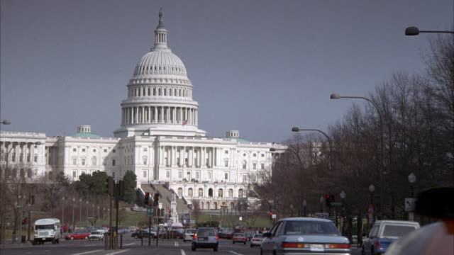 medium angle of capitol building and street in foreground. cars drive on street. - state capitol building stock videos & royalty-free footage