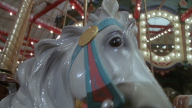 CLOSE ANGLE OF WHITE HORSE IN CAROUSEL GOING AROUND IN CIRCLES AND UP AND DOWN.