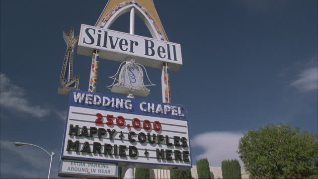 medium angle of sign that reads silver bell wedding chapel - 250,000 happy couples married here. - chapel stock videos & royalty-free footage