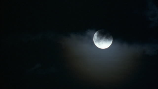 pan down of full moon in sky with black clouds covering part of moon. pans down to black sky as moon moves to exit top right. - vollmond stock-videos und b-roll-filmmaterial