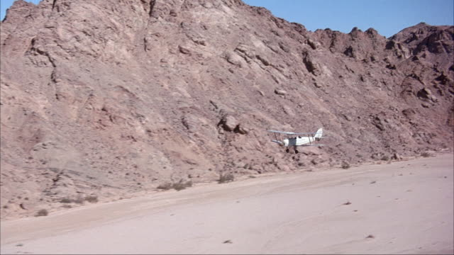 aerial of silver biplane flying over dry, arid, desert land. see rocky hills or mountains behind airplane. see flat, dry, sandy land with few bushes or shrubs below. - 複葉機点の映像素材/bロール