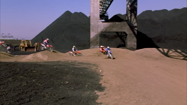 pan l-r. est. ws of dirt bike course. bikers enter from left and turn around sharp turn towards camera. pan right following bikers as they go off jump and disappear behind it. neg cut. - motocross video stock e b–roll