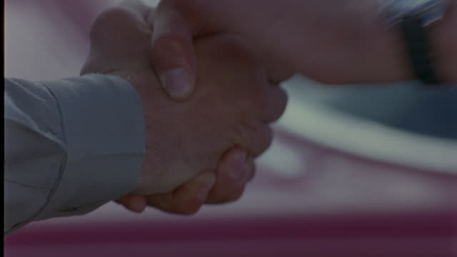 close angle of men shaking hands. man on right has money in his palm. man on left takes money during hand shake. could be drug dealers or secret business deal. - criminal stock videos & royalty-free footage