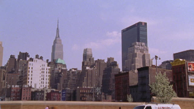 vídeos de stock e filmes b-roll de pan down from the new york city skyline to a parked limo.  the empire state building and the new yorker building can be seen. - 2001