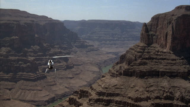 vídeos de stock, filmes e b-roll de medium angle of rear of helicopter flying through interior of grand canyon. see valley below. - grand canyon