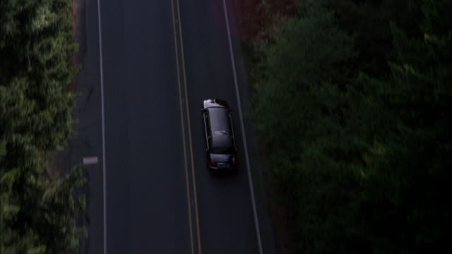 tracking shot of stretch black limo driving on two lane road through heavily wooded area. - limousine stock videos & royalty-free footage