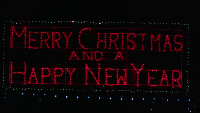 CLOSE ANGLE OF CHRISTMAS LIGHTS BLINKING RED AND GREEN ON BLUE LIGHTS. PANS DOWN TO SIGN READING MERRY CHRISTMAS AND A HAPPY NEW YEAR IN RED AND GREEN LIGHTS.