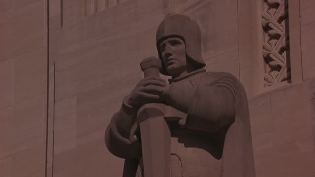 medium angle of statue in front of capitol building in baton rouge, louisiana. helmeted man holding sword. government buildings. - kapitol von louisiana stock-videos und b-roll-filmmaterial