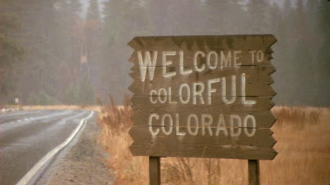 medium angle of sign that reads welcome to colorful colorado. blue station wagon drives into frame with luggage loaded on top. - welcome sign stock videos & royalty-free footage