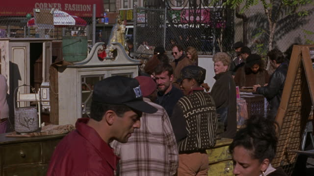 medium angle of multi-ethnic crowd at outdoor flea market. see used cabinets and chests of drawers in background. - flea market stock videos & royalty-free footage