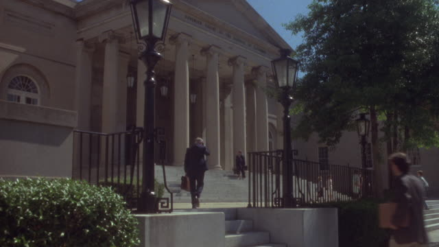 medium angle of old rockville courthouse. people walk up steps and one man walks from right foreground into frame, could be lawyers. - 弁護士点の映像素材/bロール