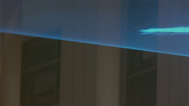 MEDIUM ANGLE OF BLUE LIGHTS OR BEAMS MOVING THROUGH AIR IN BUILDING OR LABORATORY. COULD BE PART OF LASER SECURITY SYSTEM. LIGHTS APPEAR TO MAKE WAVY SHAPES IN AIR.