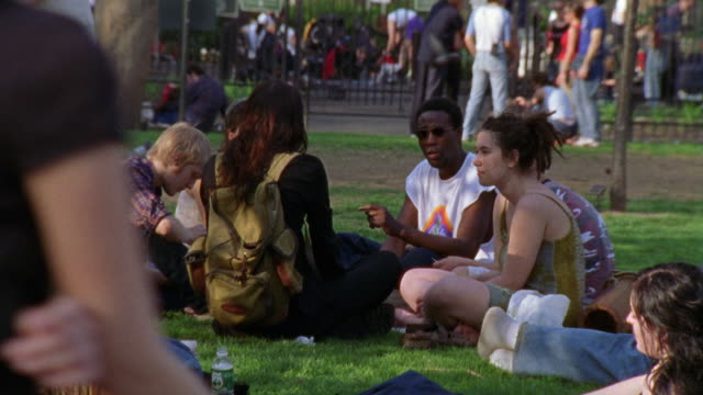 hand held angle of young men and women, maybe students sitting together in a park having a picnic. - anno 2001 video stock e b–roll