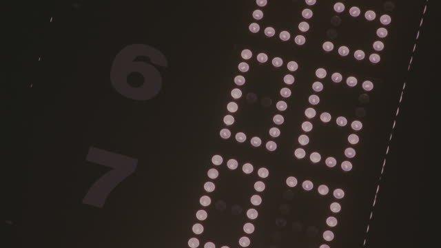 close angle of racetrack, tower, lighted scoreboard which shows race cars' positions in the race by number. racing. numbers 6 and 7 seen. - number 7 stock videos & royalty-free footage