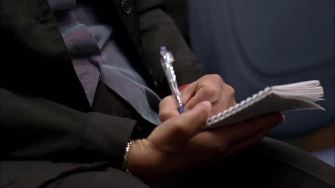 vídeos y material grabado en eventos de stock de close angle of woman reporter's hand writing on notepad with pen. pan up to woman's face as she looks up. - periodista