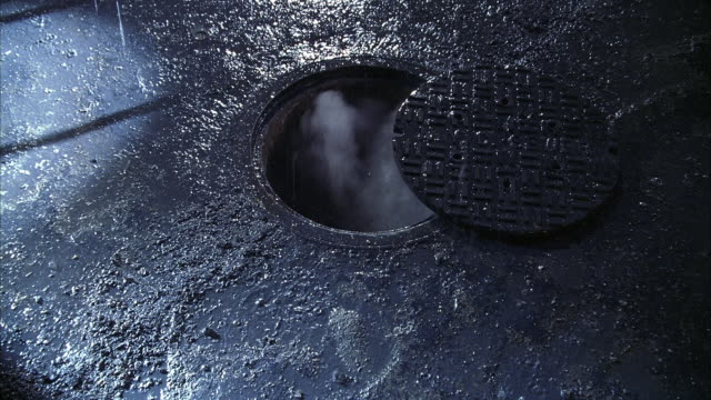 ZOOM IN AND OUT OF PARTIALLY COVERED MANHOLE. SEE STEAM ROLLING OUT AS RAIN POURS DOWN.
