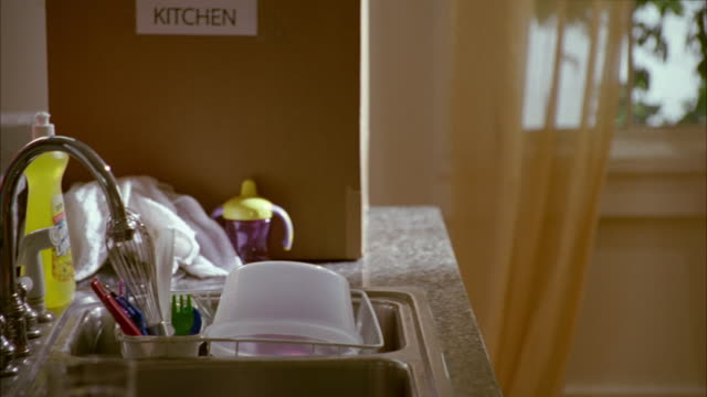 close angle of kitchen sink filled with dishes, such as tupperware and utensils. dish detergent and brillo scrub pads placed near toys, used paper towels and baby sippy cup. messy. - messy stock videos and b-roll footage