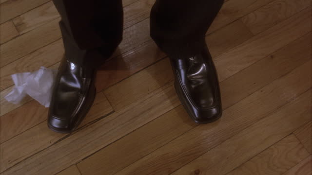 medium angle pan down on a napkin stuck on right sole of black dress shoe. right leg shakes in effort to get napkin off from shoe. insert. - black dress stock videos & royalty-free footage